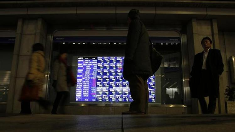 A man (C) looks at an electronic stock quotation board outside a brokerage in Tokyo January 14, 2014. REUTERS/Issei Kato