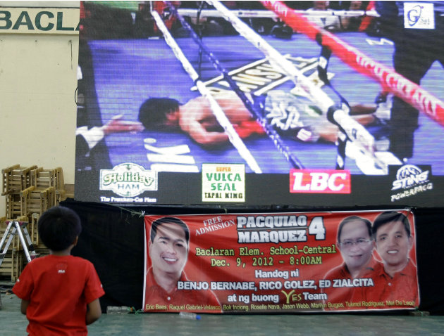 A Filipino boy watches Filipino boxing hero Manny Pacquiao lying on the mat after he was knocked out by Mexican Juan Manual Marquez during a live TV broadcast at a multi-purpose hall in suburban Paran