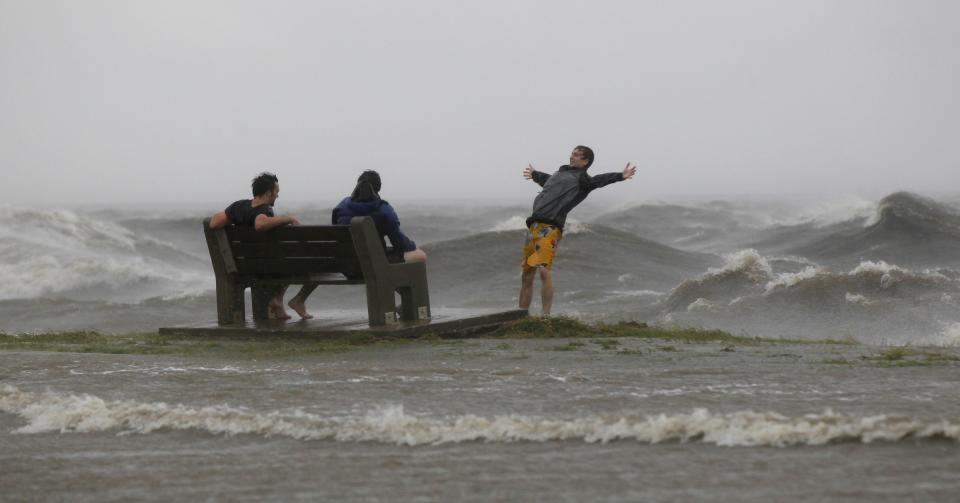 People play in the storm surge from Hurricane Isaac, on Lakeshore Drive along Lake Pontchartrain, as the storm nears land, in New Orleans, Tuesday, Aug. 28, 2012. (AP Photo/Gerald Herbert)
