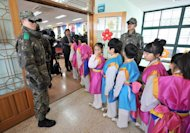 South Korean soldiers stand guard as students enter the hall during a graduation ceremony for Taesungdong Elementary School at Taesungdong freedom village near the border village of Panmunjom in Paju on February 15, 2013. Six students graduated from the only school in this South Korean village sitting inside the demilitarized zone between North and South Korea where a total of 30 students study