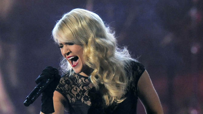 """FILE - This April 7, 2013 file photo shows Carrie Underwood performing at the 48th Annual Academy of Country Music Awards at the MGM Grand Garden Arena in Las Vegas. Underwood will take over the theme song for """"Sunday Night Football,"""" with NBC sticking to the formula of a female country music star for its intro. Underwood steps in for Faith Hill, who announced last month that she would not be back for a seventh season. Underwood will sing a new version of """"Waiting All Day for Sunday Night,"""" the network said Tuesday, May 7. (Photo by Chris Pizzello/Invision/AP, file)"""