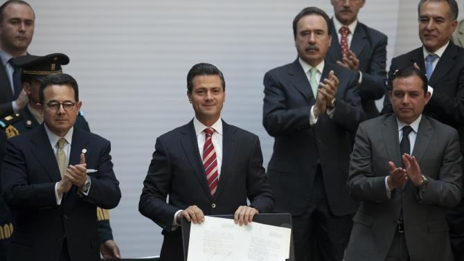 "Flanked by Mexican Senate Deputy Chairman Francisco Arroyo Vieira, left, and Mexican Senate President Ernesto Cordero, right, Mexico's President Enrique Pena Nieto, center, shows off the signed document enacting education reform, at the National Palace in Mexico City, Monday, Feb. 25, 2013. The law which was approved by Congress in December, calls for creation of a professional system for hiring, evaluating and promoting teachers without the ""discretionary criteria"" currently used in a system where teaching positions are often bought or inherited. (AP Photo/Alexandre Meneghini)"