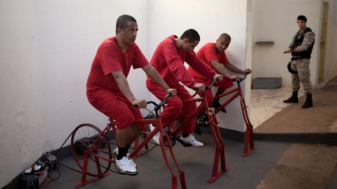 In this photo taken Friday, July  6, 2012, Ronaldo da Silva, left, and fellow inmates pedal stationary bikes to charge car batteries at a prison in Santa Rita do Sapucai, Brazil. An innovative program allows inmates at this medium-security prison to shave days off their sentence in exchange for riding stationary bikes hooked up to converted car batteries that are used to illuminate Santa Rita do Sapucai's town square. (AP Photo/Felipe Dana)