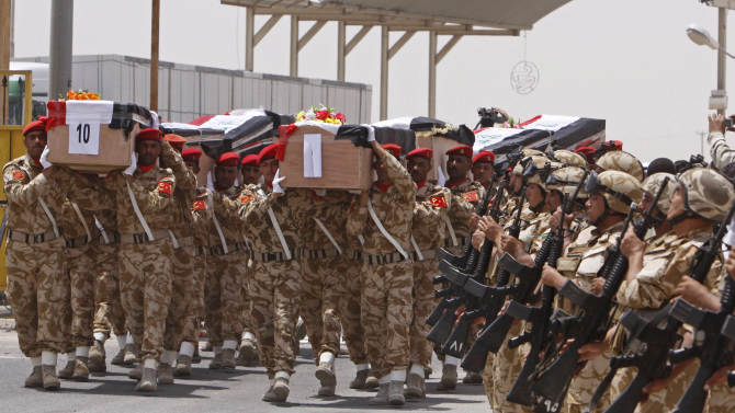 Iraqi Army soldiers carry the remains of 32 Iraqi soldiers who were killed during the 1991 Gulf war in Basra, Iraq's second-largest city, Monday, July 4, 2011. (AP Photo/ Nabil al-Jurani)