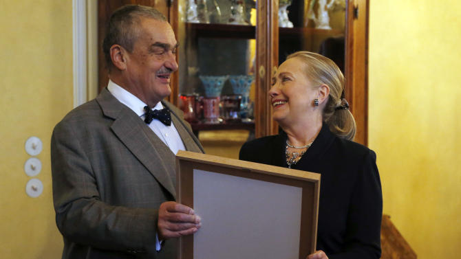 Czech Republic's Foreign Minister Karel Schwarzenberg, left, presents US Secretary of State Hillary Clinton, right, with a photograph upon her arrival in Prague, Czech Republic, Monday, Dec. 3, 2012. The photograph is picturing a meeting of Clinton and her husband Bill with late Czech Republic's President Vaclav Havel. (AP Photo/Petr David Josek)