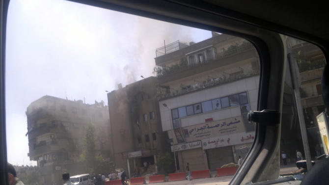 FILE - This Saturday, July 21, 2012 file citizen journalist image shot through a broken car window shows smoke billowing from a building after fighting between rebels and Syrian troops in the Yarmouk camp for Palestinian refugees in south Damascus, Syria. Syria's fighting has uprooted more than half of the country's 530,000 Palestinians — descendants of refugees from a Mideast conflict half a century ago — and their situation is becoming increasingly desperate, the head of a U.N. aid agency said Thursday, May 23, 2013. The Palestinians in Syria are particularly vulnerable because of their refugee status, Filippo Grandi, head of the U.N. Relief and Works Agency, told The Associated Press in an interview. (AP Photo, File)