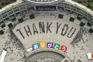 "An aerial view shows people sitting in formation to the words ""thank you"" and displaying signs that collectively read ""Arigato"" during an event celebrating Tokyo being chosen to host the 2020 Olympic Games, in Tokyo"