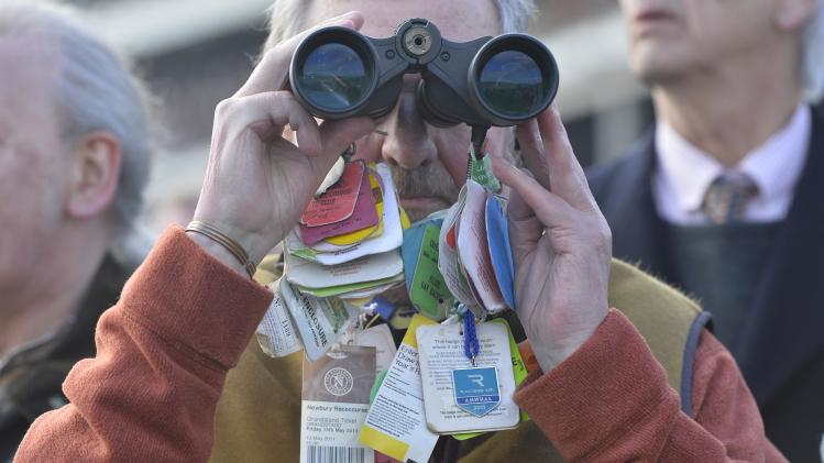 A racegoer looks through his binoculars with race tags attached at the Cheltenham Festival horse racing meet in Gloucestershire, western England