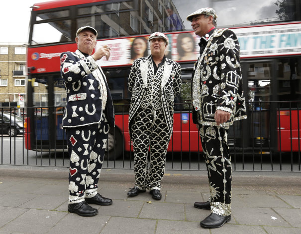 CAPTION CORRECTION, CORRECTS SPELLING OF NAME TO JUKES NOT JUKER - John Scott, the Pearly King of Mile End, left, Jimmy Jukes, the Pearly King of Camberwell and Bermondsey, center, and Shaun Austin, the Pearly King of Tower Hamlets talk outside a pub in London's Tower Hamlets Borough Thursday, July 19, 2012. The Pearly Kings were at the pub for an event to promote the Cockney language and culture in London's East End as the city prepares for the 2012 Summer Olympics. (AP Photo/Charlie Riedel)