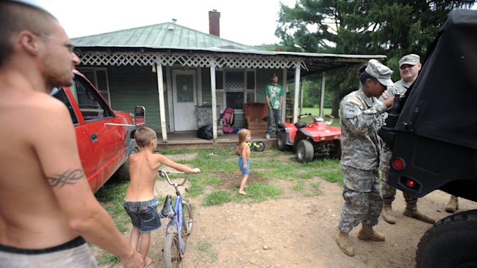 National Guard Sgt. Jessica Homeres, second from right, and Spc. Jeremy Lemaster, far right, prepare to deliver food and water to a home Thursday, July 5, 2012 in Heaters, W.Va. While utility crews continued working to restore power, members of the West Virginia National Guard went door to door with firefighters, police, church groups and others to reach people who were still awaiting help. Residents in the Heaters area have been without power since Friday, June 29, 2012 following a severe storm.  (AP Photo/Jeff Gentner)