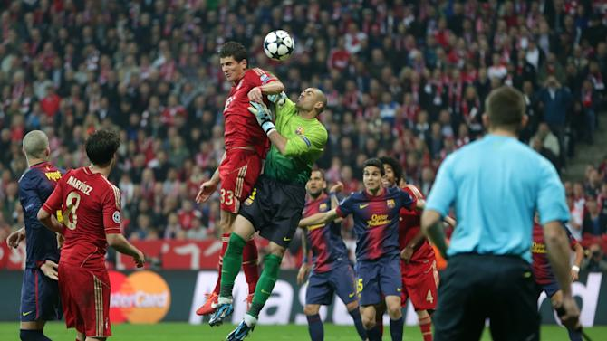 Bayern's Mario Gomez, center left, jumps for the ball with Barcelona's goalkeeper Victor Valdes during the Champions League semifinal first leg soccer match between Bayern Munich and FC Barcelona in Munich, Germany, Tuesday, April 23, 2013. (AP Photo/Matthias Schrader)