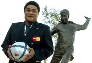 File photo of Portuguese soccer player Eusebio holding a soccer ball and posing in front of his statue at the entrance of the Luz Stadium in Lisbon