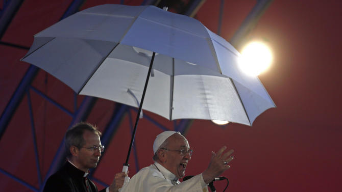 Side lit by a stage light Pope Francis addresses the youth gathered at the World Youth Day Welcome Feast on the Copacabana beachfront in Rio de Janeiro, Brazil, Thursday, July 25, 2013. Francis addressed the young pilgrims from 175 nations gathered on the famous beach. Francis is on the fourth day of his trip to Brazil. Holding the umbrella is Vatican Master of Ceremonies, Mons. Guido Marini. (AP Photo/Stefano Rellandini, Pool)