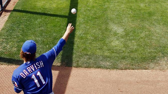 Texas Rangers pitcher Yu Darvish warms up prior to his first appearance in a spring training baseball game against the San Diego Padres, Wednesday, March 7, 2012, in Peoria, Ariz. (AP Photo/Matt York)