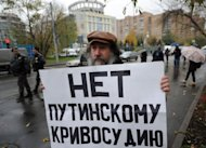 "A protester holds a poster reading: ""No to Putin's Justice!' near the court in Moscow"