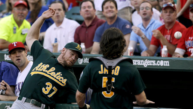 Texas Rangers' Josh Lindblom, left, and Oakland Athletics' John Jaso (5) watch as Brandon Moss (37) slams into the fence in front of the Rangers dugout trying to reach a Nelson Cruz foul ball in the second inning of a baseball game Tuesday, June 18, 2013, in Arlington, Texas. (AP Photo/Tony Gutierrez)