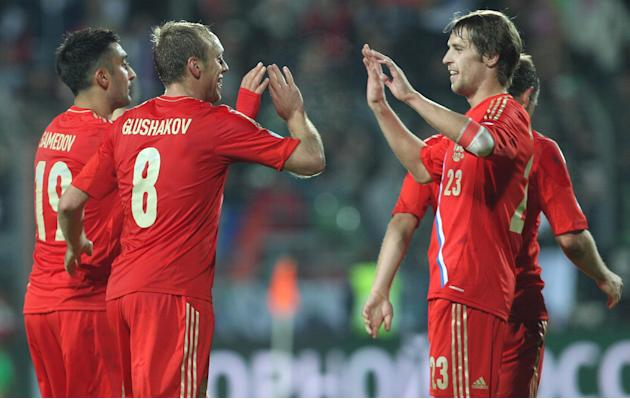 Russia's Denis Glushakov, second left, gets congratulations by his team mates, after he scored, during the World Cup 2014 Group F qualifying soccer match against Luxembourg, in Luxembourg city, at the