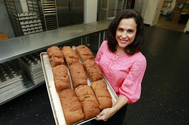 In this Thursday, July 14, 2012 photo, Michele Kelly, owner of Pure Knead bakery, poses with a rack of freshly baked gluten-free sandwich bread in Decatur, Ga. A research team led by the Mayo Clinic&#39;s Dr. Joseph Murray looked at blood samples taken from Americans in the 1950s and compared them to samples taken from people today, and determined celiac disease, triggered by gluten, has been increasing, confirming estimates that about 1 percent of U.S. adults have it today, Murray and his colleagues reported Tuesday, July 31, 2012. (AP Photo/John Bazemore)
