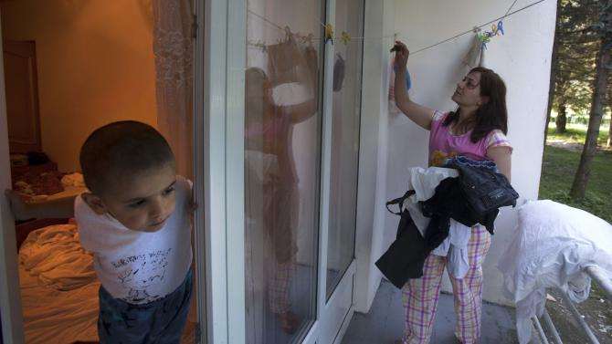 In this Monday, July 23, 2012 photo, Rem Kray, right, a refugee from the Syrian city of Aleppo, takes down the laundry as her son, Adam, looks at her from a hotel room in Nalchik, Russia, Monday, July 23, 2012. Some 340 ethnic Circassians from Syria have come to Russia's Caucasus region this year. Czarist troops and Cossacks expelled hundreds of thousands of Circassians in the 1860s in what some historians call a genocide and an ethnic cleansing. (AP Photo/Misha Japaridze)