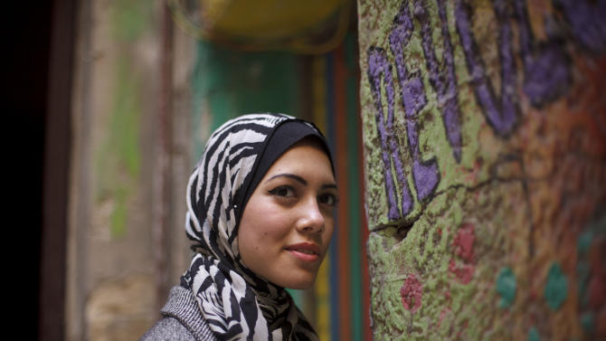 """In this Tuesday, Dec. 10, 2013 photo, Egyptian rapper Myam Mahmoud poses for a portrait in downtown Cairo. Mahmoud, an 18-year-old Egyptian, rapped her way to the semi-finals of the Middle East's hit TV show """"Arabs Got Talent."""" While she didn't win the program, Mahmoud did succeed in throwing a spotlight on something more than just herself. On a very public stage, her songs pulled back the curtain on the slew of challenges that women across the Arab world are fighting to overcome. """"I wanted to tell girls in Egypt and everywhere else that they are not alone, we all have the same problems, but we cannot stay silent, we have to speak up,"""" Mahmoud told The Associated Press during an interview at her home. (AP Photo/Maya Alleruzzo)"""