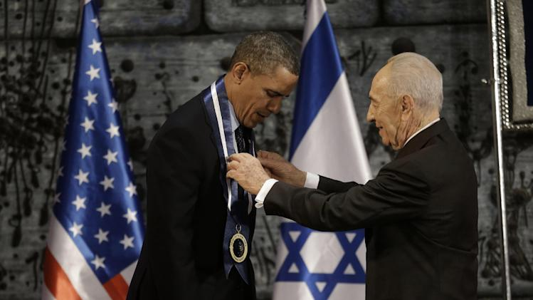 President Barack Obama receives the Israeli Medal of Distinction from Israeli President Shimon Peres, Thursday, March 21, 2013, at a State Dinner at President's residence in Jerusalem, Israel, Thursday, March 21, 2013, (AP Photo/Pablo Martinez Monsivais)