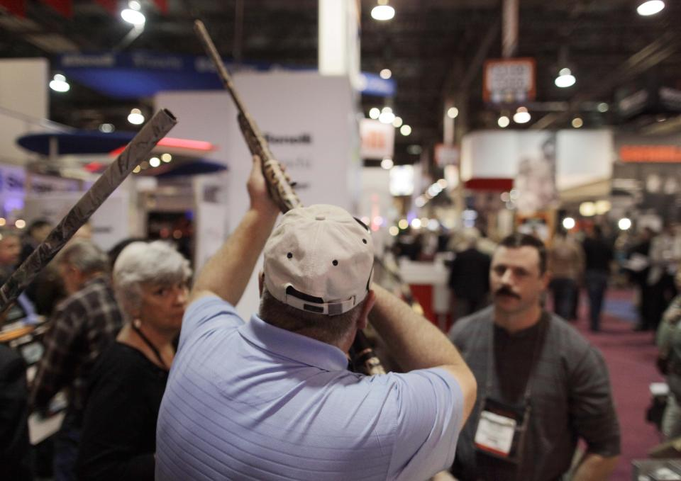 An industry retailer looks down the sight of a hunting rifle at the Shooting, Hunting and Outdoor Trade show, Tuesday, Jan. 18, 2011 in Las Vegas. (AP Photo/Julie Jacobson)