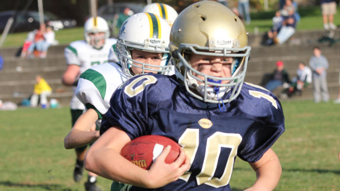 In this 2012 photo provided by Marycecelia Pla, her daughter, Caroline Pla, foreground, carries the ball during a Catholic Youth Organization league football game. The 11-year-old girl who's been playing football since kindergarten wants Philadelphia's Roman Catholic archdiocese to overturn a boys-only rule. (AP Photo/Pla Family)