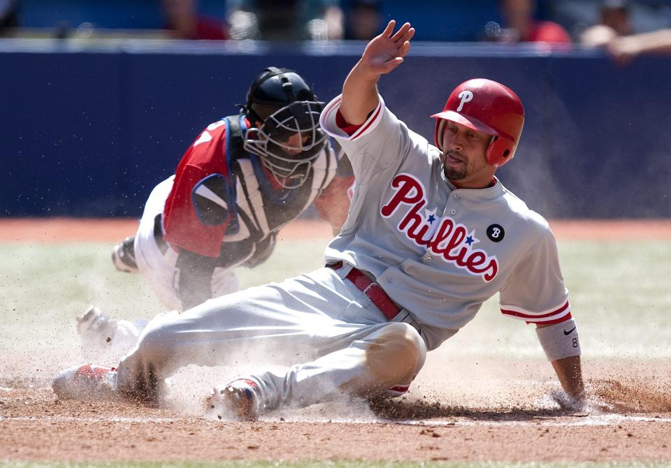 Philadelphia Phillies' Shane Victorino, foreground, steals home plate in front of Toronto Blue Jays catcher J.P Arencibia after a sacrifice fly from Ben Francisco during the seventh inning of a baseball game, Friday June 1, 2011, in Toronto. (AP Photo/The Canadian Press, Chris Young)