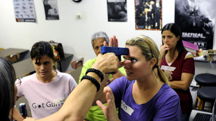 A group of local public school teachers from nearby schools use rubber training guns as they practice drills on disarming an attacker  during a teachers-only firearms training class offered for free at the Veritas Training Academy in Sarasota