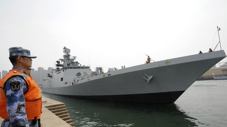 A Chinese navy personnel stands guard as Indian naval frigate INS SHIVALIK is seen docked at a military port after its arrival before a maritime drill during the Western Pacific Naval Symposium in Qingdao