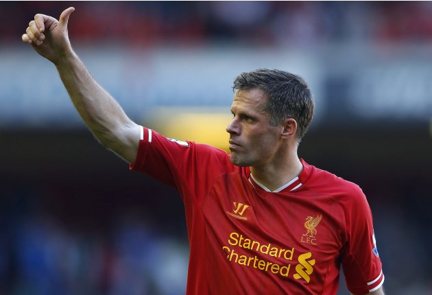 Liverpool's Carragher waves to the crowd as he walks around the pitch following their English Premier League soccer match against Queens Park Rangers in Liverpool