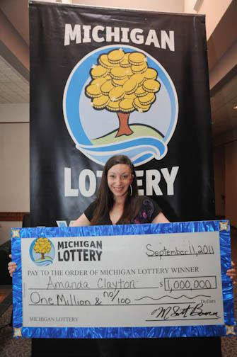 FILE - In this March 8, 2012 file photo provided by the Michigan Lottery, Amanda Clayton holds her $1 million lottery check. Clayton, who continued to get food stamps after winning a $1 million lottery jackpot, has been charged with welfare fraud. The Michigan attorney general's office announced two felony charges Tuesday, April 17, 2012 against Clayton of Lincoln Park. She was arrested Monday and was expected to be arraigned Tuesday in Lincoln Park's 25th District Court. (AP Photo/courtesy Michigan Lottery via Detroit Free Press)