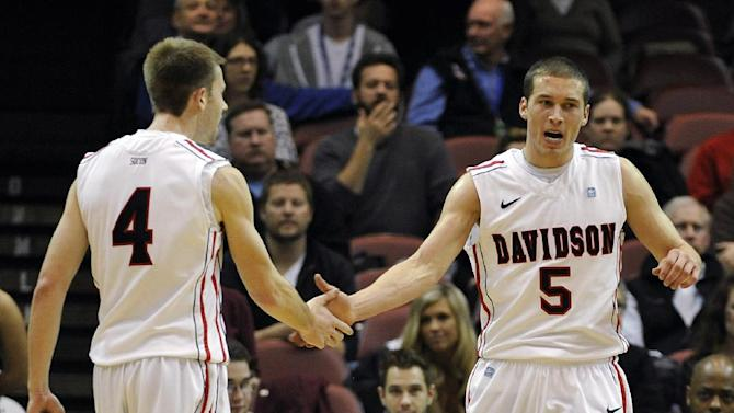 Davidson's JP Kuhlman (5) celebrates with teammate Tyler Kalinoski (4) after scoring against College of Charleston in the first half of an NCAA basketball game during the Southern Conference tournament on Monday, March 11, 2013 in Asheville, N.C. (AP Photo/Rainier Ehrhardt)