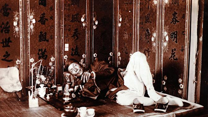 """In this photo taken in about 1920 and released by American author Steven Martin, a Chinese man smokes in a very upscale opium den in China. One Halloween night, in a blacked-out bedroom in Bangkok's Chinatown, Steven Martin went into physical and mental free fall. High fever oscillated with shivering cold, gut-wrenching stomach pains brought on waves of diarrhea. Howling in agony, he leapt around the room in a kind of devil dance, his body smeared with oily sweat, vomit, mucus and feces. """"Opium Fiend, A 21st Century Slave to a 19th Century Addiction''  opens with this harrowing description of the author trying to cut himself off from a drug that had taken over his life as a freelance journalist in Southeast Asia. Although Martin doesn't advocate the use of opium,  his memoir is no simple cautionary tale, nor was he  your ordinary backpacker junkie, such as still roam this region of cheap and plentiful drugs. (AP Photo/Courtesy of Steven Martin) EDITORIAL USE ONLY, NO SALES"""
