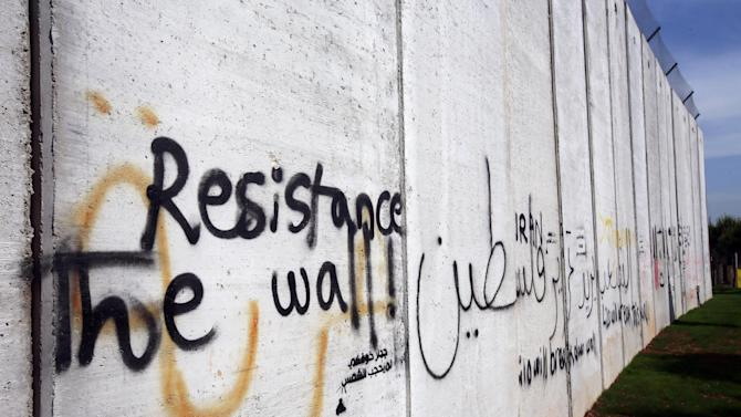 """In this picture taken on Thursday May 23, 2013, Arabic words reading: """"the people need to liberate Palestine,"""" are written on a wall that was built by Israel at Fatima Gate, where Hezbollah supporters from all over Lebanon and beyond held some of their demonstrations against Israel, in the southern village of Kafr Kila, Lebanon. A year ago, Israel built the wall along the town's stretch of the border, blocking the view of its territory and ruining the main show in town and destroying the business of the Fatima Gate Restaurant and Gift Shops. In the eerily quiet south, the battle in Qusair seems far away as most residents of towns and villages nervously watch Israeli army patrols drive along the border, their bases tucked away just behind a metal fence. (AP Photo/Hussein Malla)"""