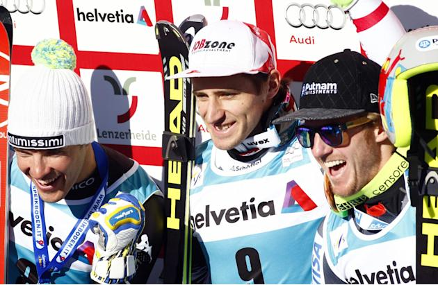 Austria's Matthias Mayer, center, the winner, second-placed Italy's Christof Innerhofer, left, and third-placed  Ted Ligety, of the United States, celebrate after a men's alpine skiing dow