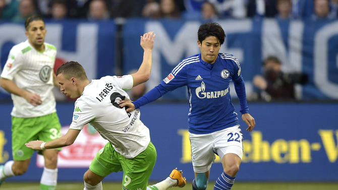 Schalke's Atsuto Uchida from Japan, right, and Wolfburg's Ivan Perisic from Croatia  challenge for the ball during the German Bundesliga soccer match between Schalke 04 and VfL Wolfsburg in Gelsenkirchen,  Germany, Saturday, Nov. 22, 2014