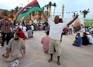 In Libyen hatte mehr als vier Jahrzehnte lang Gaddafi unumschränkt geherrscht. Er war in Folge eines Volksaufstandes vor knapp einem Jahr gestürzt und und am 20. Oktober 2011 auf der Flucht getötet worden. Die Macht im Land übernahm der Nationale Übergangsrat. Die ersten freien Wahlen in Libyen wurden am 7. Juli abgehalten. A Libyan man holds the Libyan flag as others gather to celebrate the first anniversary, according to the Islamic calender, of the start of the uprising against former leader Moamer Kadhafi, and break their fast in Martyr's Square, in Tripoli, during the Muslim holy month of Ramadan on August 8, 2012. Kadhafi was captured and killed on October 20, 2011, while trying to flee Sirte, his hometown and the last major city to fall to Western-backed rebels who rose up against his regime nine months earlier. AFP PHOTO/MAHMUD TURKIA