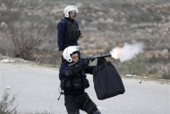 A Palestinian policeman fires tear gas towards demonstrators outside the Jalazoun refugee camp near the West Bank city of Ramallah January 12, 2014. REUTERS/Mohamad Torokman