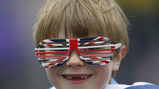 Owen Lewis, 7, looks on at Tower Bridge as thousands of people gather along the river Thames in London waiting for Britain's Queen Elizabeth II flotilla of boats to sail pass in a river pageant as part of a four-day Diamond Jubilee celebration to mark the 60th anniversary of  Queen Elizabeth II accession to the throne, Sunday, June 3, 2012. (AP Photo/Sang Tan)