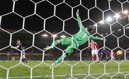 Manchester City's James Milner scores past Asmir Begovic of Stoke City during their English Premier League soccer match at the Britannia Stadium in Stoke-on-Trent, central England