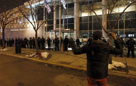 A protester shouts derogatory slogans at Chicago police officers standing guard outside the District 1 Police headquarters in Chicago, Illinois