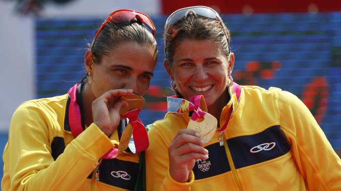 Brazil's Juliana Silva, left, and Larissa Franca show their gold medals on the podium of the women's beach volleyball event at the Pan American Games in Puerto Vallarta, Mexico, Friday, Oct. 21, 2011. (AP Photo/Ariana Cubillos)