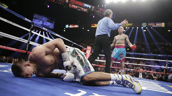 England's Amir Khan, left, crumbles to the mat after receiving a low blow from Luis Collazo, right, in their silver welterweight title boxing fight Saturday, May 3, 2014, in Las Vegas. Referee Vic Drakulich is at center. Khan went on to win by unanimous decision. (AP Photo/Isaac Brekken)