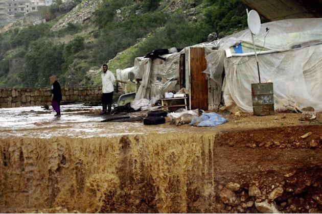 A Lebanese farmer stands near his dead goats after his herd was by hit heavy rains and big wind on January 7, 2013 in the Lebanese southern city of Jadra. Heavy rains have hit the region making six pe