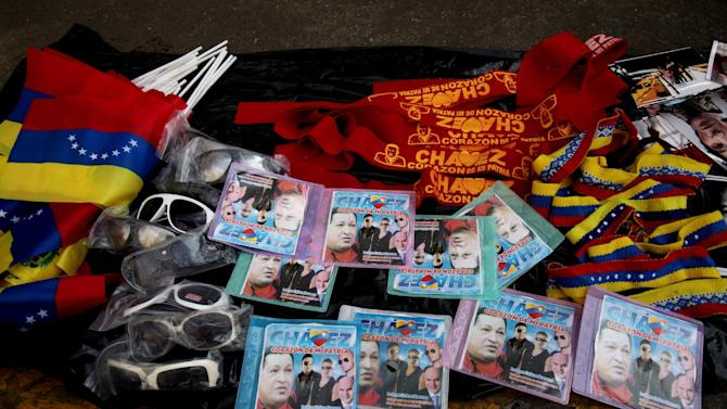 Hugo Chavez souvenirs sit for sale during a rally in Caracas, Venezuela, Wednesday, Jan. 23, 2013. Filling the void of Chavez's 6-week absence following a fourth surgery in Cuba, the government has been churning out a steady stream of emotional images, slogans and Chavez sound bites that appear poised to solidify Chavez's legacy as a messianic savior of the poor. (AP Photo/Fernando Llano)