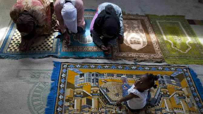 In this Sept. 28, 2012 photo, Christine Brazile sits on a prayer as her relatives pray during Friday prayer service at the Al-Fattah Mosque in Gressier, Haiti.  Islam has won a growing number of followers in this impoverished country, especially after the catastrophic earthquake in 2010 that killed hundreds of thousands and left millions more homeless. (AP Photo/Dieu Nalio Chery)