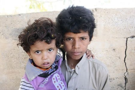 Mohammed Saleh Qayed Taeiman poses for a photo with his younger brother outside their family's house in Marib province