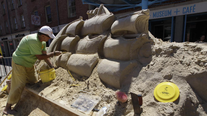 Master Sand Sculptor Matthew Long works on repairing a sand sculpture outside the South Street Seaport museum, Saturday, June 16, 2012 in New York. The sculpture was vandalized Friday night. (AP Photo/Mary Altaffer)
