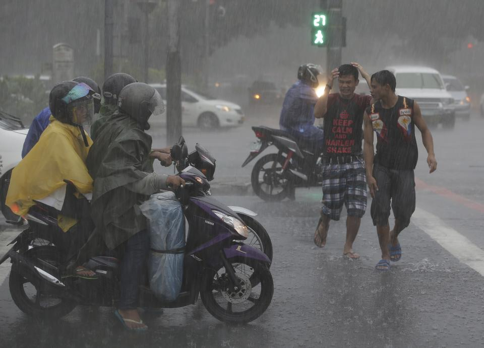 Filipino men cross the street during heavy rain in Manila, Philippines Sunday, Sept. 22, 2013. The year's most powerful typhoon had Hong Kong in its crosshairs on Sunday after sweeping past the Philippines and Taiwan and pummeling island communities with heavy rains and fierce winds. (AP Photo/Aaron Favila)
